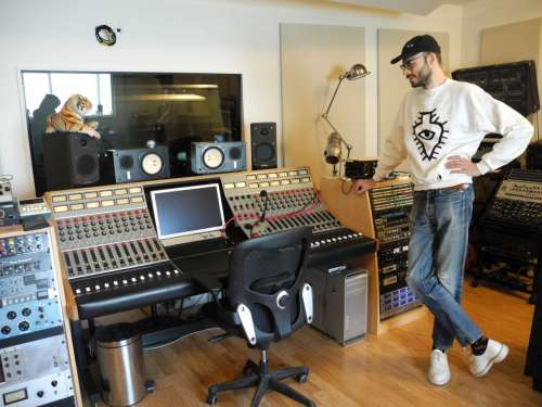 Joakim standing over a soundboard in his studio, Crowd Spacer, in Brooklyn, NY