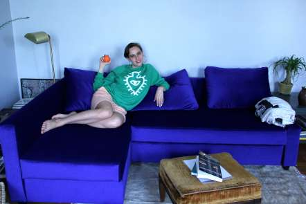Camilla Wasserman reclining on a couch and holding an orange wearing a Luaka Bop sweatshirt