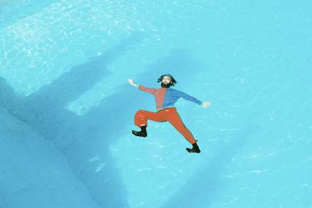 Photograph of Thor Rixon in an orange and blue long sleeve shirt and bright organge pants floating in a bright blue pool