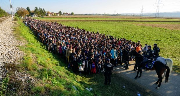 Police forces stop asylum seekers on their way to a refugee center after crossing the Croatian-Slovenian border near Rigonce on October 24, 2015.