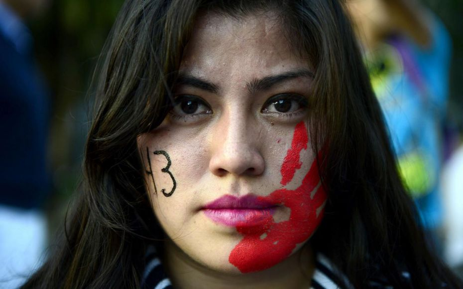 A woman protests, the body count and blood marked on each side of her face.